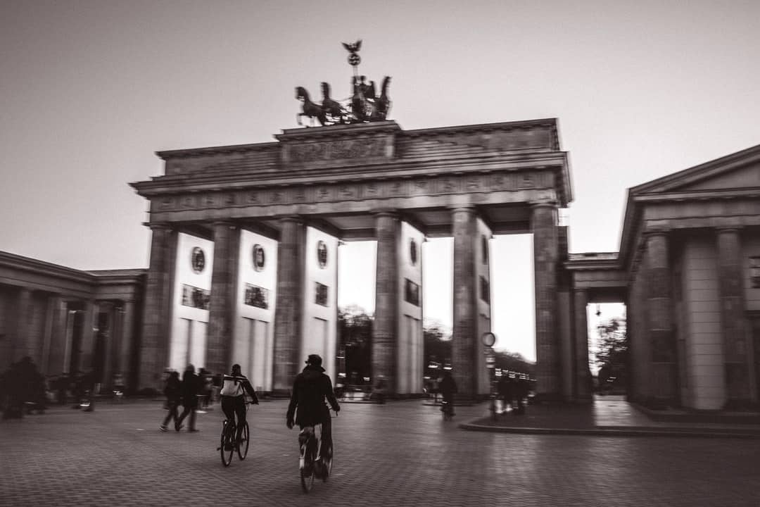 A group of people walking on a brick building with Brandenburg Gate in the background