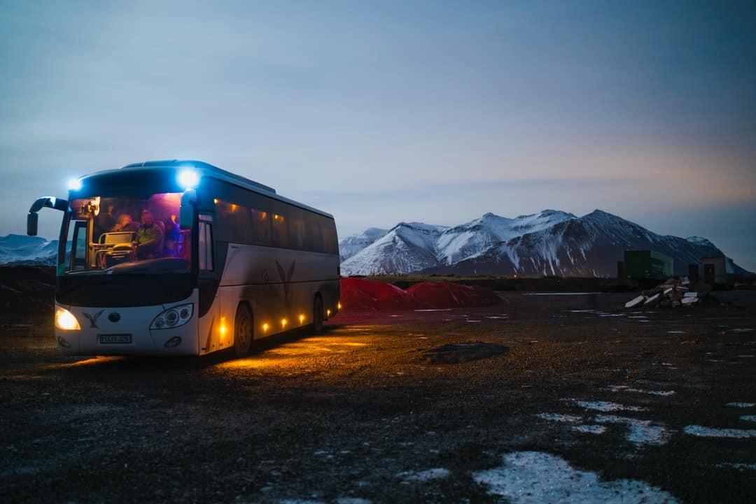 A bus parked in front of a sunset