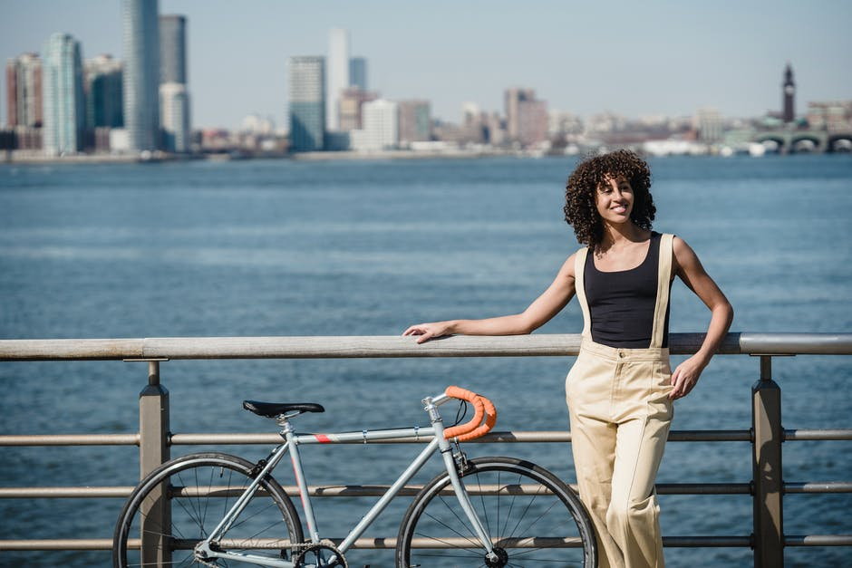 A person with a bicycle in front of a body of water